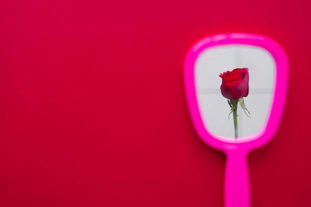 Flor rosa vermelha no reflexo do espelho na mesa Foto gratuita