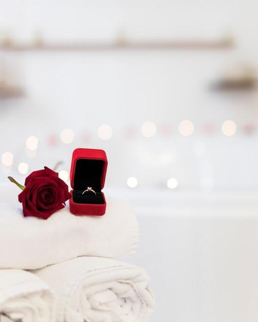 Flor, toalhas e anel na caixa de jóias perto de banheira de hidromassagem com velas Foto gratuita