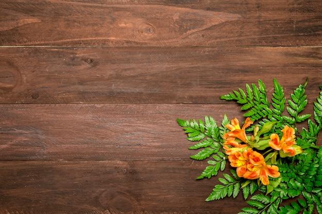 Flores alaranjadas com folhas no fundo de madeira Foto gratuita