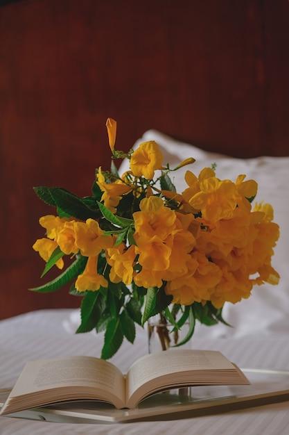 Flores amarelas com um livro em uma bandeja branca em uma cama de hotel Foto Premium