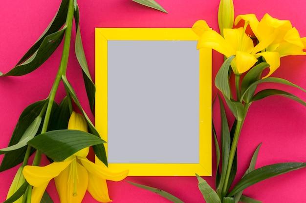 Flores amarelas do lírio e moldura para retrato vazia sobre o rosa; fundo Foto gratuita