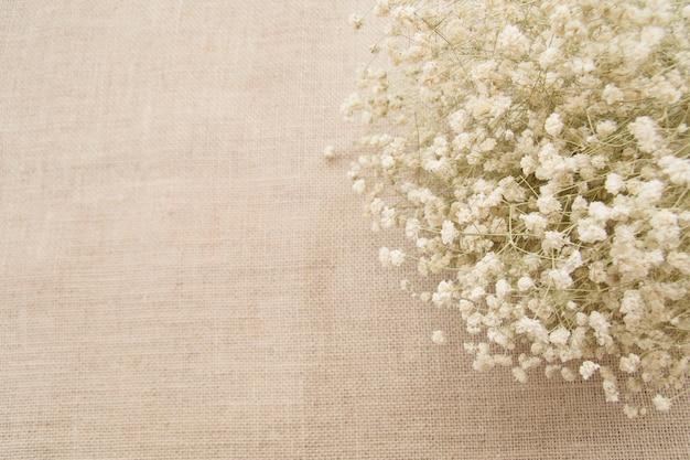 Flores brancas com espaço de cópia no fundo de textura de saco Foto Premium
