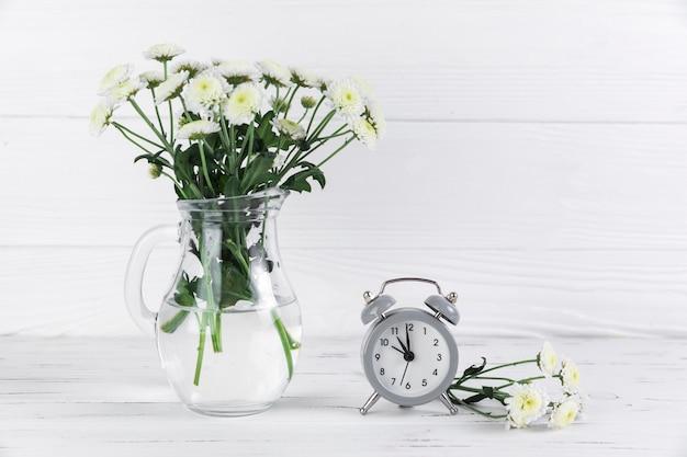 Flores brancas de crisântemo em jarra de vidro perto do pequeno despertador na mesa de madeira Foto gratuita