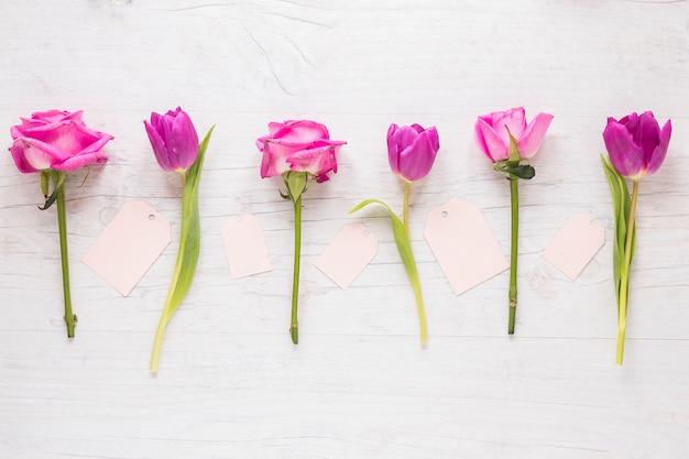 Flores brilhantes com pequenos papéis na mesa Foto gratuita