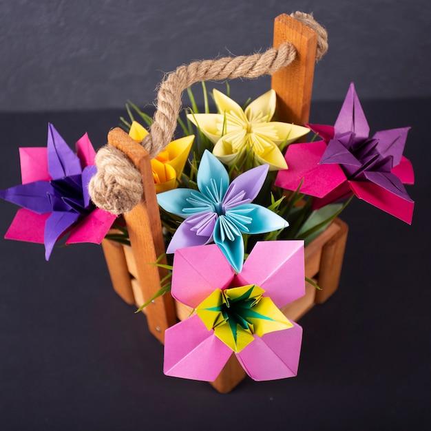 Flores coloridas artesanais origami buquê papel artesanato arte em uma cesta com no estúdio na macro fundo colorido Foto Premium