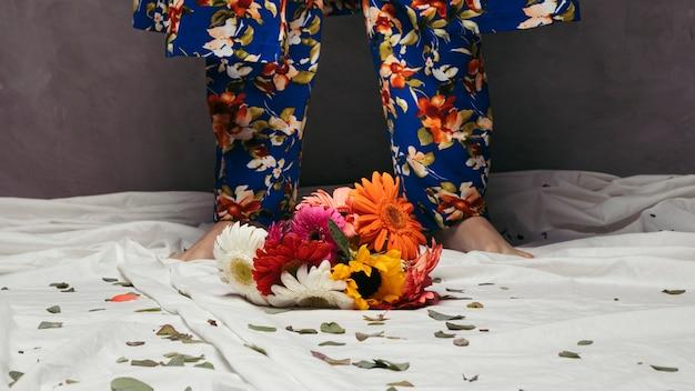 Flores coloridas gerbera na frente do pé do homem Foto gratuita