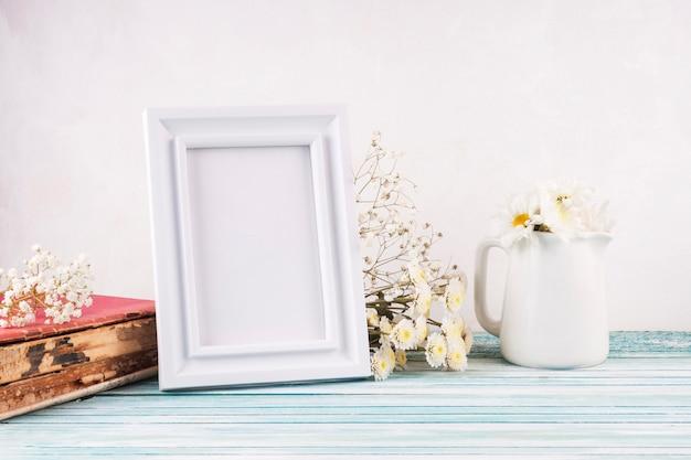 Flores com moldura em branco na mesa de madeira Foto gratuita