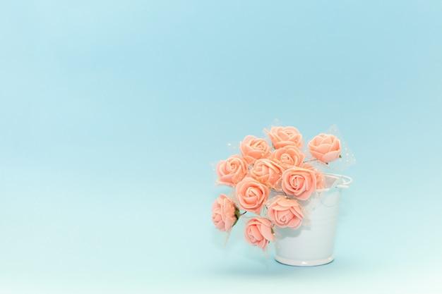 Flores cor de rosa em um balde de brinquedo branco sobre um fundo azul claro, flores para o feriado Foto Premium