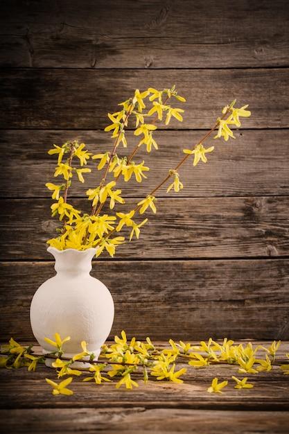 Flores da primavera amarelo sobre fundo de madeira velho Foto Premium