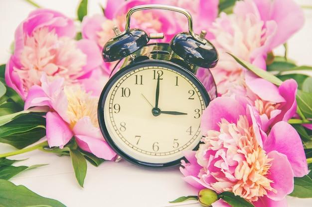 Flores da primavera e despertador. mude a hora. Foto Premium