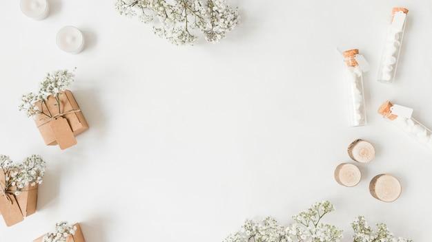Flores da respiração do bebê; caixas de presente; velas e tubo de ensaio com marshmallow no pano de fundo branco Foto gratuita