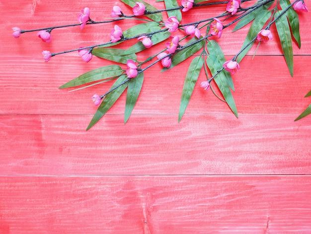 Flores de flor-de-rosa e folhas de bambu verde sobre fundo vermelho de madeira Foto Premium