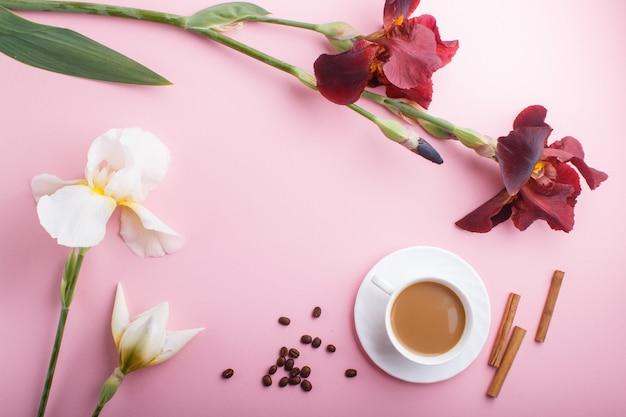 Flores de íris branca e bordeaux e uma xícara de café em rosa pastel Foto Premium
