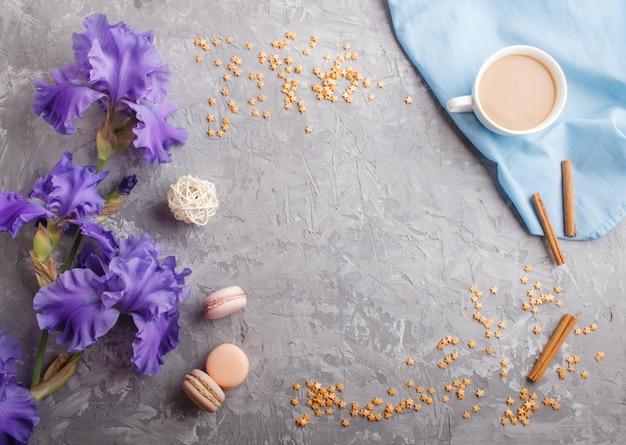 Flores de íris roxas e uma xícara de café em concreto cinza Foto Premium