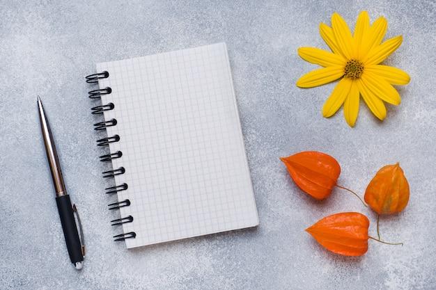 Flores de outono e o bloco de notas para o texto em cima da mesa com espaço de cópia Foto Premium