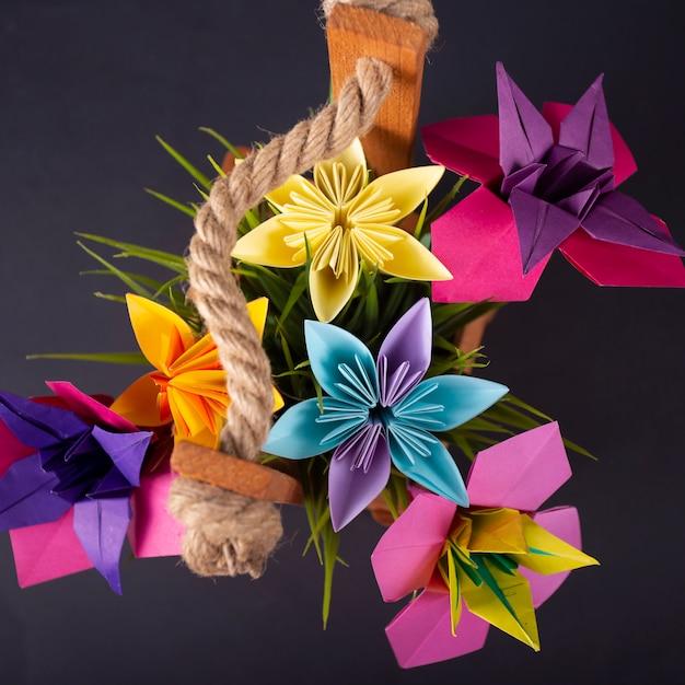 Flores de papel colorido artesanal origami buquê papel artesanato arte em uma cesta com grama no estúdio em blackbackground Foto Premium