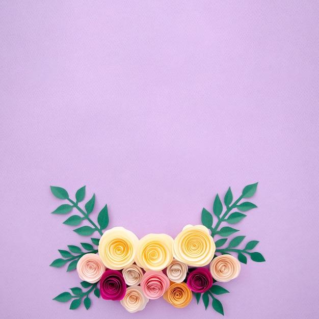 Flores de papel de vista superior e folhas no fundo roxo Foto gratuita