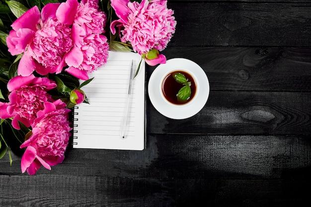 Flores de peônia em fundo preto com nota ou diário um Foto Premium