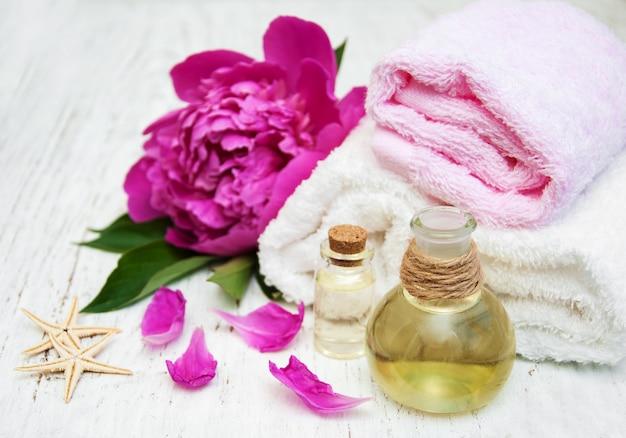 Flores de peônia, óleos de massagem e toalhas Foto Premium