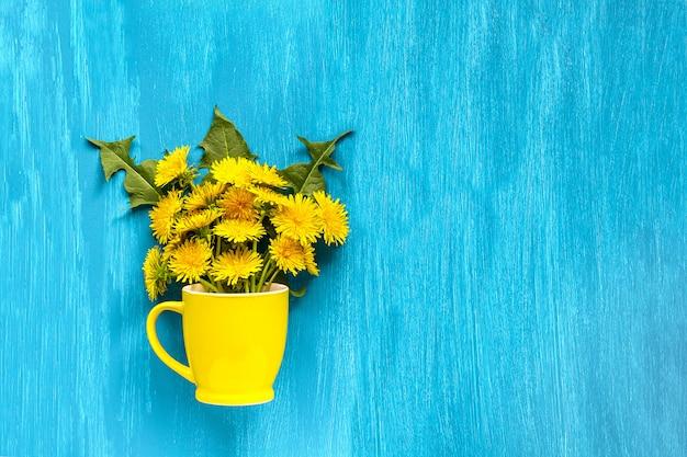 Flores de ramalhete leão taraxacum em caneca amarela sobre fundo azul de madeira Foto Premium