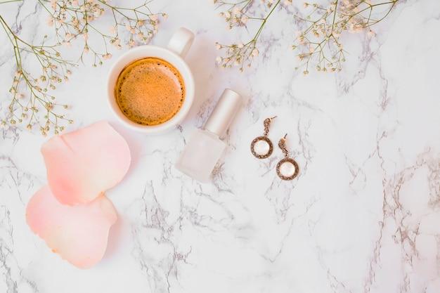 Flores de respiração do bebê com pétalas de rosas; xícara de café; garrafa de verniz de unhas e brincos em pano de fundo texturizado em mármore branco Foto gratuita