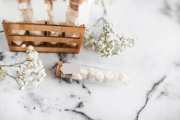 Flores de respiração do bebê e tubos de ensaio de marshmallow no plano de fundo texturizado Foto gratuita