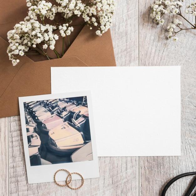 Flores de respiração do bebê no envelope com papel em branco; alianças de casamento e quadro polaroid Foto gratuita