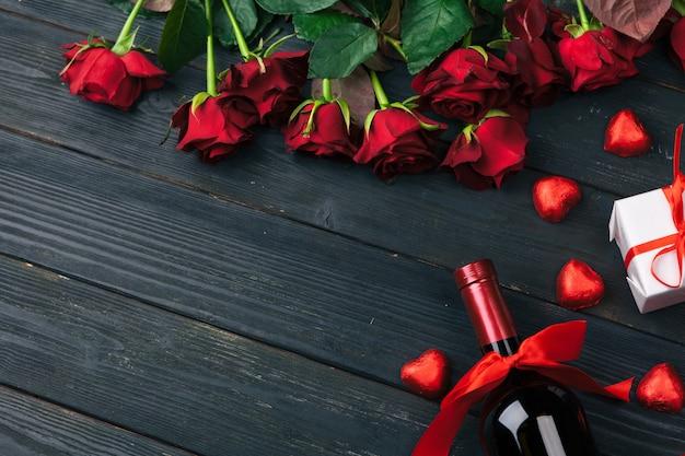 Flores de rosas vermelhas, vinho e caixa de presente na mesa de madeira. Foto Premium