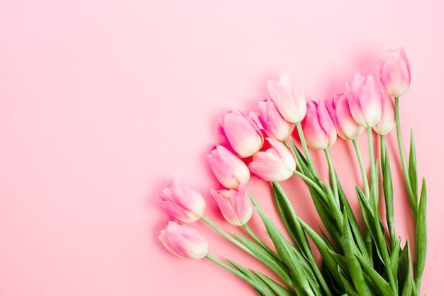 Flores de tulipa brilhante na mesa-de-rosa Foto gratuita