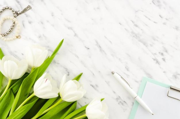 Flores de tulipa com prancheta e pulseiras Foto gratuita