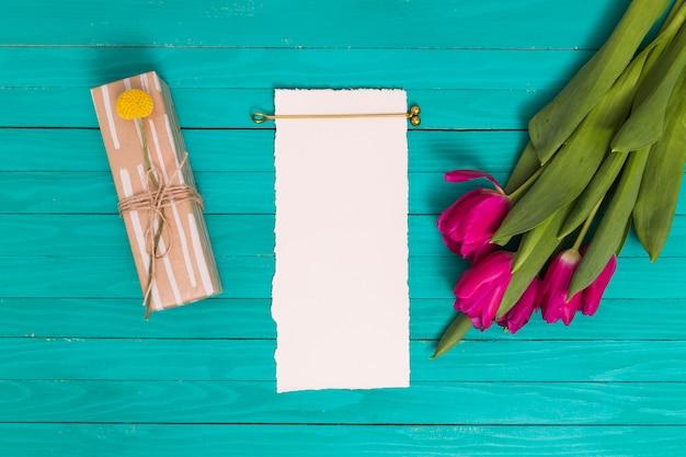 Flores de tulipa rosa; caixa de presente; e papel branco em branco sobre fundo verde Foto gratuita
