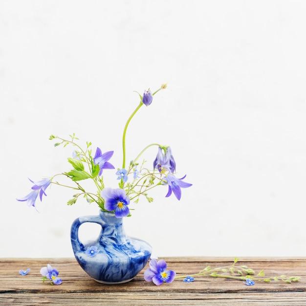 Flores de verão no jarro azul na mesa de madeira velha Foto Premium