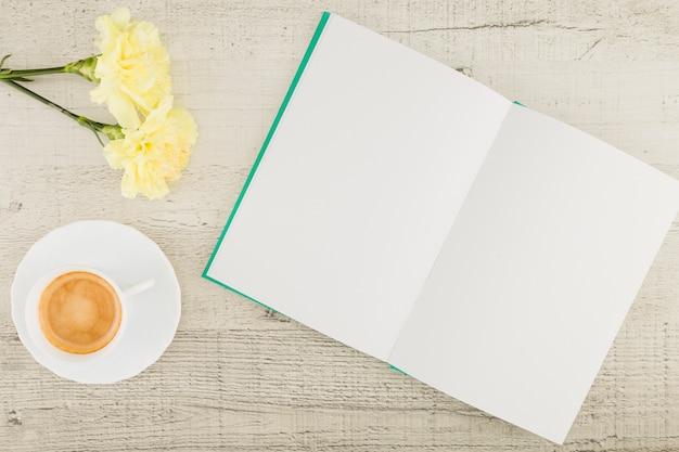 Flores de vista superior com livro sobre fundo de madeira Foto gratuita