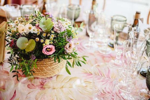 Flores decorando as peças centrais com talheres de luxo nas mesas de um salão de festas. Foto Premium