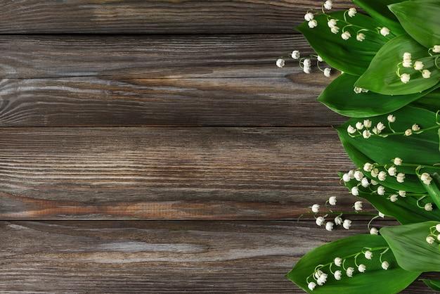 Flores do lírio do vale em madeira rústica. vista do topo. configuração plana Foto Premium