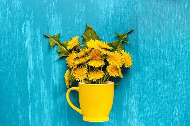Flores do taraxacum dos dentes-de-leão do ramalhete na caneca amarela Foto Premium