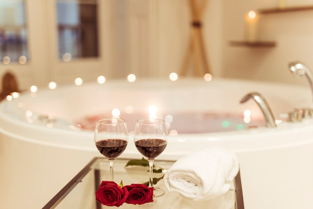 Flores e copos de bebida perto da banheira de hidromassagem com água e velas acesas nas bordas Foto gratuita