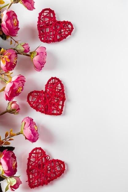 Flores e corações vermelhos em um fundo branco para o dia dos namorados. quadro de corações e flores sobre fundo branco, lugar para texto. design para o dia dos namorados, foto vertical Foto Premium
