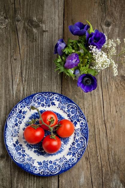 Flores e prato com tomate fresco Foto Premium