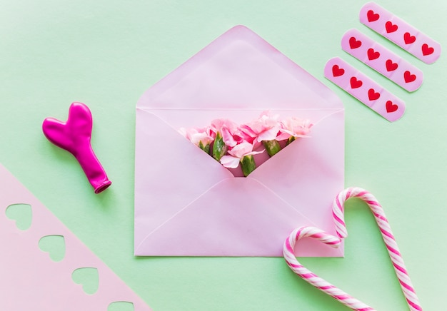 Flores em envelope com bastões de doces Foto gratuita