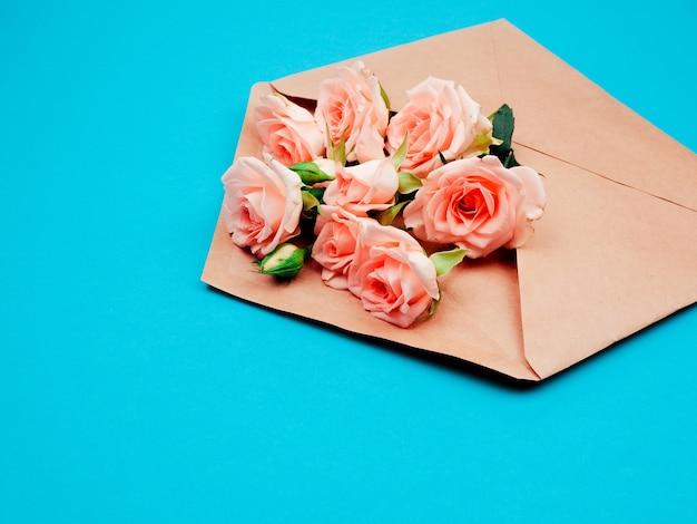 Flores em um envelope kraft, cópia espaço, fundo azul Foto Premium