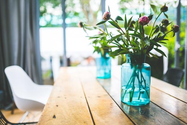 Flores em um vaso azul na mesa Foto Premium