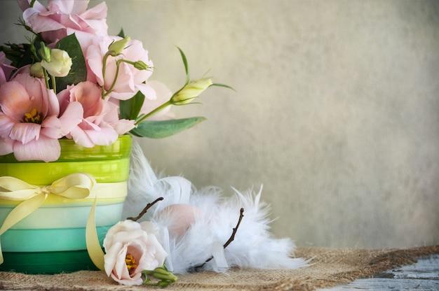 Flores em um vaso com fita amarela e ovo em penas Foto Premium