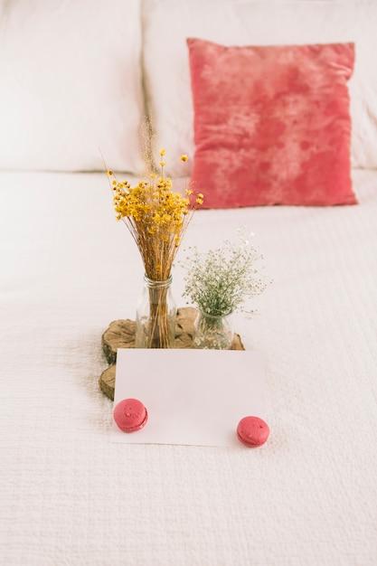 Flores em vasos com macaroons e papel Foto gratuita