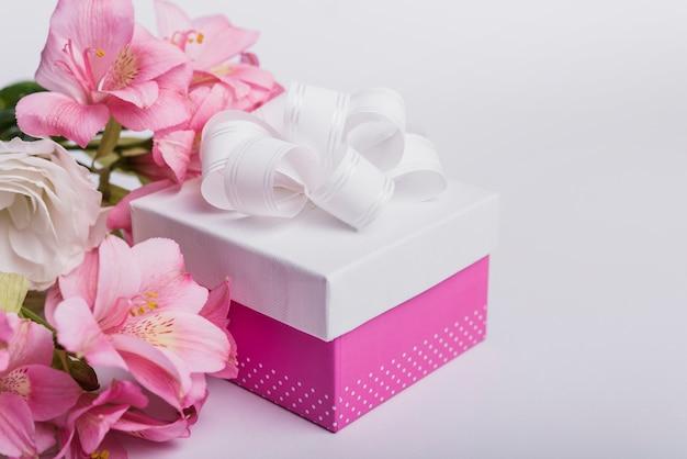 Flores frescas e caixa de presente no fundo branco Foto gratuita