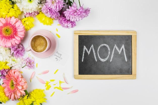 Flores frescas perto de copo de bebida, lousa com palavras de mãe e pétalas Foto gratuita