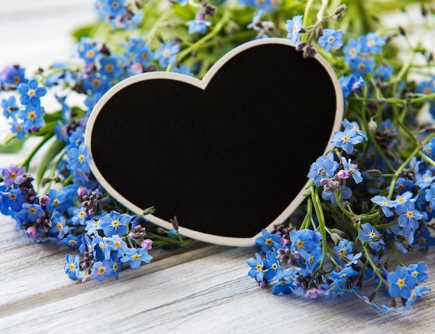 Flores miosótis e quadro em forma de coração preto sobre fundo branco de madeira Foto Premium