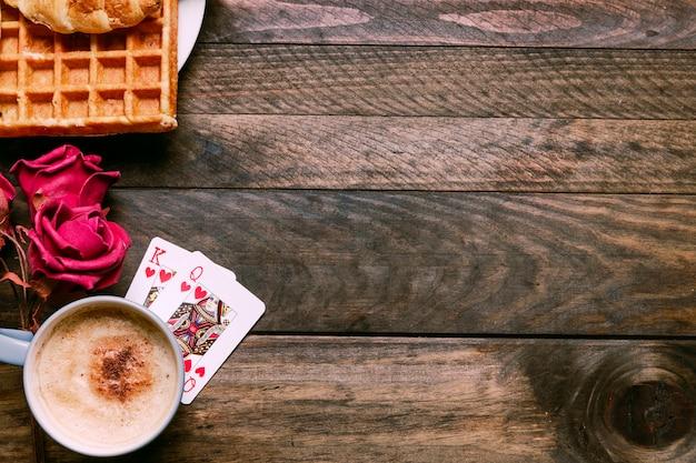 Flores, padaria no prato, cartas de baralho e copo de bebida Foto gratuita