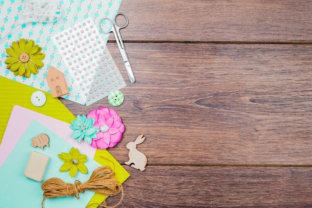 Flores; papel; pérolas; botão e linha com uma tesoura na mesa de madeira Foto gratuita