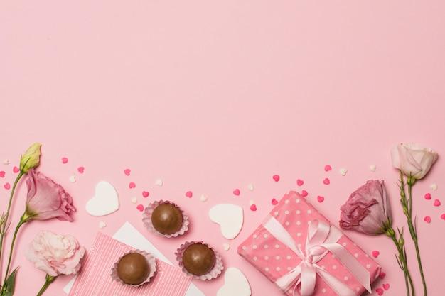 Flores perto de cartão postal na caixa de presente e bombons de chocolate Foto gratuita
